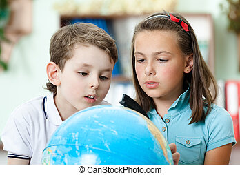 Two friends examine a school globe trying to find something
