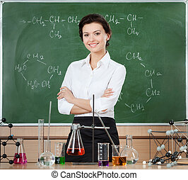 Smiley chemistry teacher is surrounded with chemical glassware