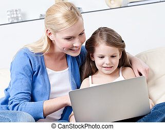Little child surfs on the internet with her mother