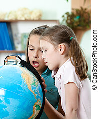 Pupils look at the globe in wide-eyed astonishment - Two...