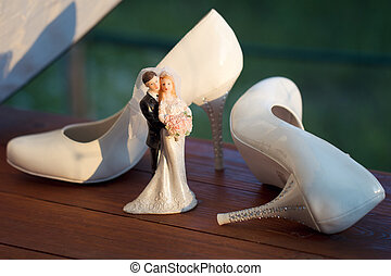 bridal shoes near the bride and groom figurines