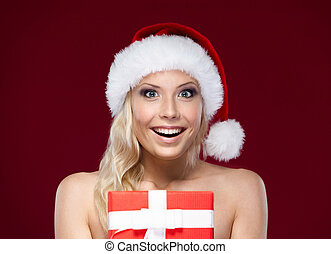 Pretty woman in Christmas cap hands present