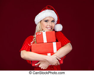 Young woman in Christmas cap hands a set of presents wrapped with red paper, isolated on purple