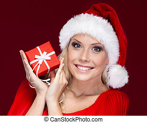 Attractive woman in Christmas cap hands a present