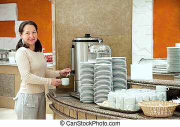 Woman pours coffee from coffee machine