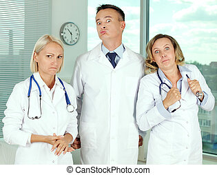 Irritation - Three clinicians in white coats looking angrily...