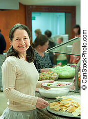 Woman chooses  snack  in buffet