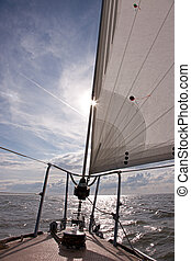 Sailing - Looking into the bright sun from the bow of a...