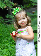Apple Consumption - Little girl holds an apple that she is...