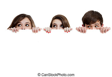 Three teenagers peeking over a white background with copy...