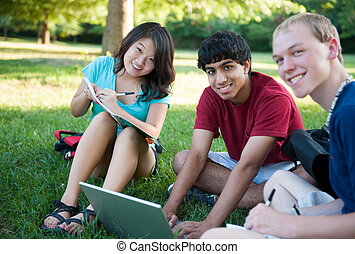 Group of three happy teenagers studying - A group of three...
