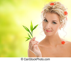 Beautiful blond woman with young plant.
