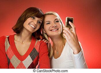 Two beautiful girls making self-portrait using mobile phone