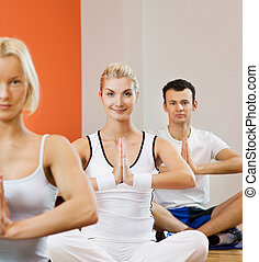 Group of people doing yoga exercise (focus on a woman in the...