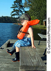 Safety first - Small boy sits on a wooden dock wearing a...