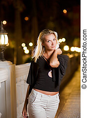 Beautiful young woman relaxing outdoors at night