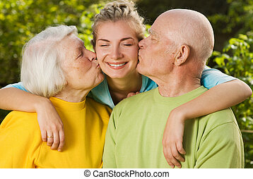 Grandparents kissing their granddaughter
