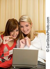 Two beautiful women having fun working with on laptop