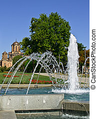 Belgrade fountain in Tasmajdan park with orthodox church of...