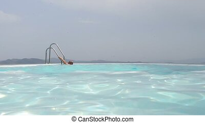 Pool loop - Man, surfacing in an infinity pool via the...