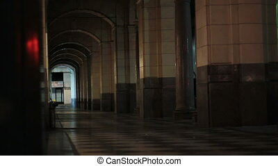 urban perspective walk - A man walks down a dark arched...