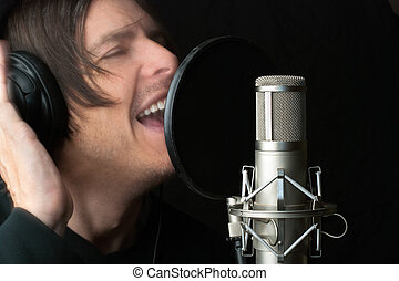 Man Records Vocals In Studio - Close-up of a man recording...