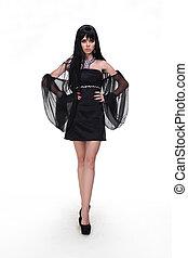 Fashion woman model wearing black dress with wing