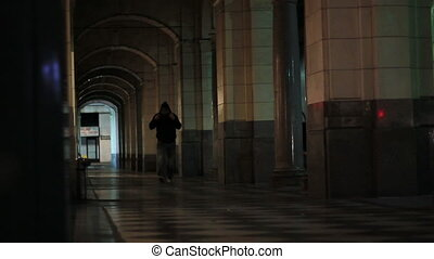 urban perspective walk 2 - A man walks down a dark arched...