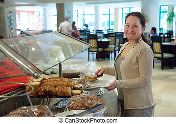 Mature woman chooses sweet pastry