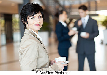 businesswoman having coffee break - middle aged...