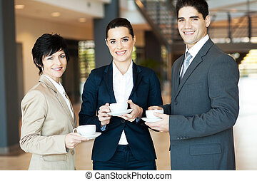 group of colleagues having coffee break at work