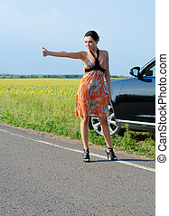 Woman hitchhiking after a breakdown - Elegant woman in a...
