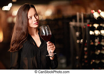 Sommelier - Young girl with a glass of wine in the cellar