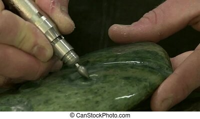 Carving Greenstone 2. - Hands of a carver working greenstone...