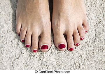 Red toenails - Woman feet with red toenails on natural beach...