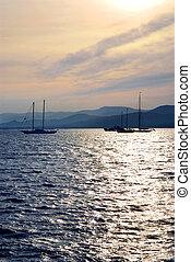 Anchored sailboats at sunset at Mediterranean coast