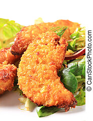 Crispy chicken tenders with salad greens