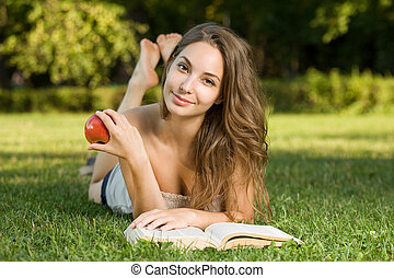 Cute young brunette in the park reading. - Portrait of a...