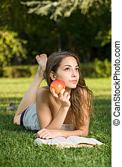 Cute young brunette in the park reading - Portrait of a cute...