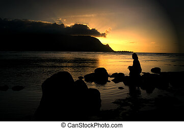 Brilliance at Sunset - Woman sits alone on a beach at...