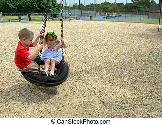 Childhood Memories - Brother and sister swing together on a...