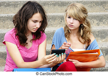 Cyber or online bullying concept with two young women...