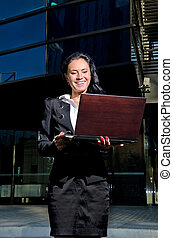 Businesswoman with notebook in front of office building