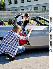 Male thief stealing handbag from the car while his...