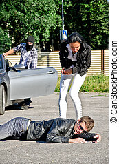 Male thief stealing a car while his accomplice distracts...