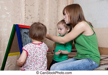 Woman and children draws on blackboard - Woman and children...