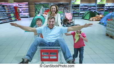 Superdad - Mom and two kids wheeling daddy in the market...