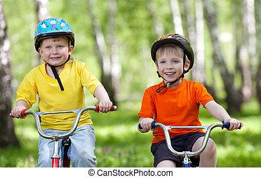 little children riding their bikes