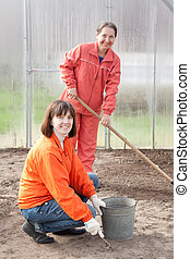 Happy women works at greenhouse