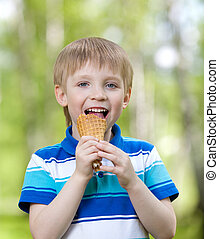 child boy  eating a tasty ice cream outdoors